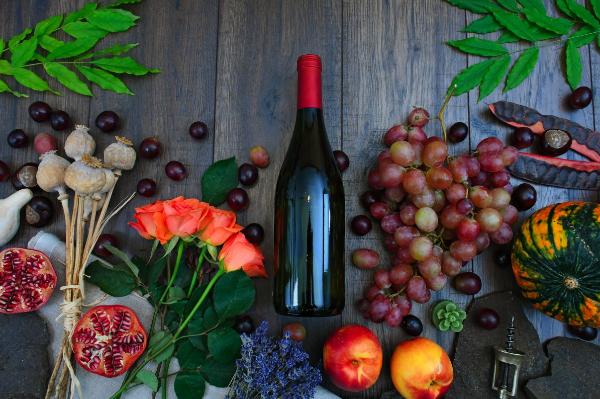 Bouteille de vin au milieu de fleurs, fruits et légumes