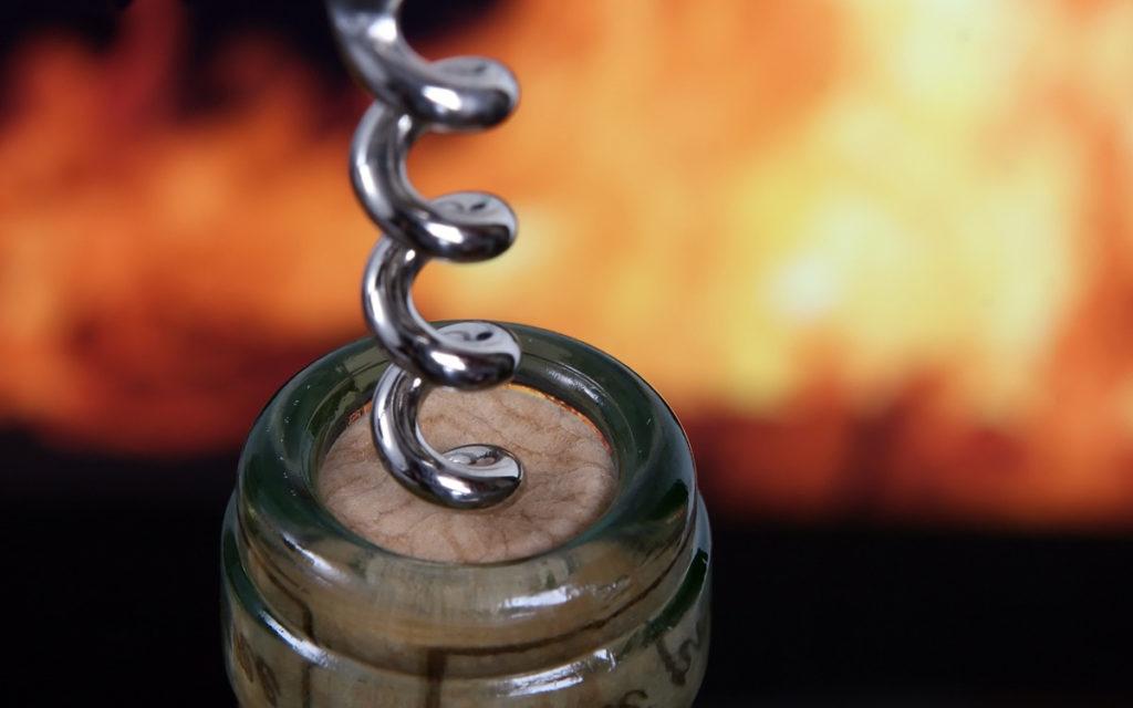 bouteille de vin en train d'être ouverte devant les flames d'un bbq