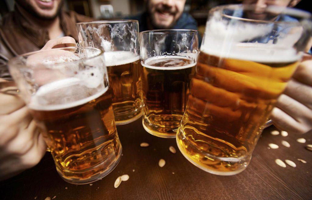 Trinquer entre amis ou collègues dans un bar avec des pintes de bière